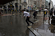 Storm Georgina swept across parts of Britain and in central London, lunchtime office workers were caught out by torrential rain and high winds, on 24th January 2018, in London, England. Pedestrians resorted to leaping across deep puddles at the junction of New Oxford Street and Kingsway at Holborn, the result of overflowing drains. Third in a sequence of five photos