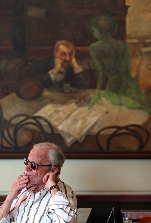 """Gast im ber¸hmten Kaffeehaus SLAVIA in der Prager Innenstadt. Im Hintergrund das Gem‰lde """"Der Absinthtrinker"""" von Maler Viktor Oliva.<br /> <br /> Visitor at the famous CafÈ Slavia in the city centre of Prague. In the back a painting by Viktor Oliva with the title Absinth drinker."""