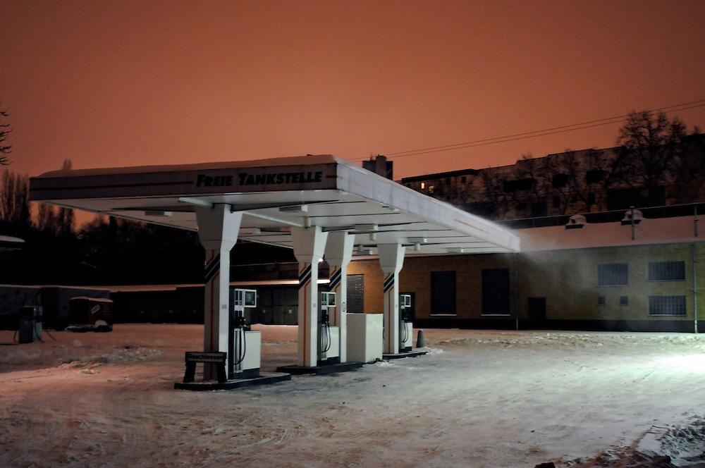 Eine freie verschneite Tankstelle im nächtlichen Winter an Heilig Abend in Köln | A gas station covered in snow  in Cologne Germany in a winter night