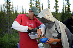 "Dene First Nation Youth Damian Kailek, left,  and Brendan Felix Head, eat the last scraps of food on the final day of a journey  to the Upper Thelon River, where their ancestors believe is ""the place where God began.""  Sparsely populated, today few make it into the Thelon. Distances are simply too far, modern vehicles too expensive and unreliable. For the Dene youth, faced with the pressures of a western world, the ties that bind the people and their way of life to the land are even more tenuous. Every impending mine, road, and dam construction threatens to sever these connections. In July and August, 2011 a group of youth paddled to their ancestral hunting ground and spiritual abode.  this next generation of young leaders will be the ones who will need to speak for the Thelon the loudest. (Photo by Ami Vitale)"