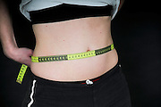 Young Woman measures her waist. She may be keeping track of weight loss during a diet but compulsive body analysis may be a symptom of a body image disorder such as anorexia nervosa. Model released