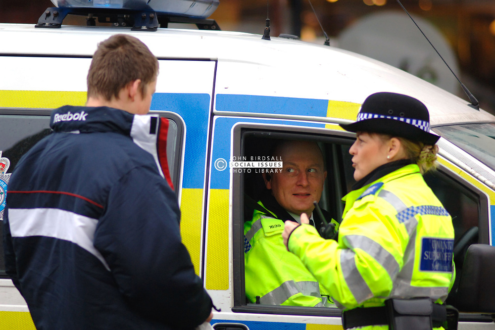 Female Community Support Officer and policeman in patrol van speak to a male youth; Yorkshire UK