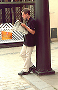 Man age 25 leaning against pole reading newspaper.  Poznan Poland