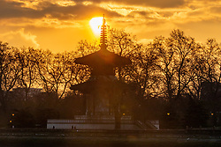 © Licensed to London News Pictures. 11/02/2021. London, UK. Sunrise over the Peace Pagoda in Battersea Park, South West London as the Met Office issue weather warnings for extreme cold with temperatures dropping to as low as -10c last night in the South East as Storm Darcy continues to bring freezing weather and travel chaos to the UK.  Photo credit: Alex Lentati/LNP