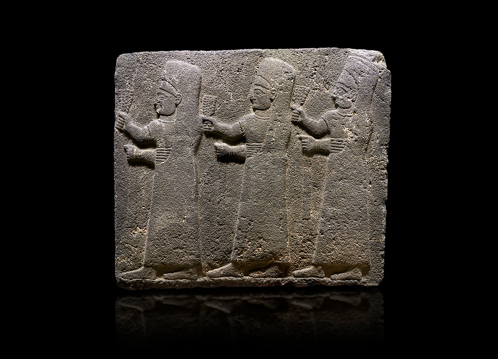 Hittite monumental relief sculpted orthostat stone panel of a Procession Basalt, Kargamis, Gaziantepe, 900 - 700 B.C. Anatolian Civilisations Museum, Ankara, Turkey.<br /> <br /> It is a depiction of three marching female figures in long dress with a high headdress at their head. These women are considered to be the nuns of the Goddess Kubaba. The figures in the front and behind have a bunch of spicy in their right hand while the figure in the middle has an empty right hand. Figures carry objects similar to a sceptre in their left hand. <br /> <br /> Against a black background. .<br />  <br /> If you prefer to buy from our ALAMY STOCK LIBRARY page at https://www.alamy.com/portfolio/paul-williams-funkystock/hittite-art-antiquities.html  - Type  Karkamıs in LOWER SEARCH WITHIN GALLERY box. Refine search by adding background colour, place, museum etc.<br /> <br /> Visit our HITTITE PHOTO COLLECTIONS for more photos to download or buy as wall art prints https://funkystock.photoshelter.com/gallery-collection/The-Hittites-Art-Artefacts-Antiquities-Historic-Sites-Pictures-Images-of/C0000NUBSMhSc3Oo