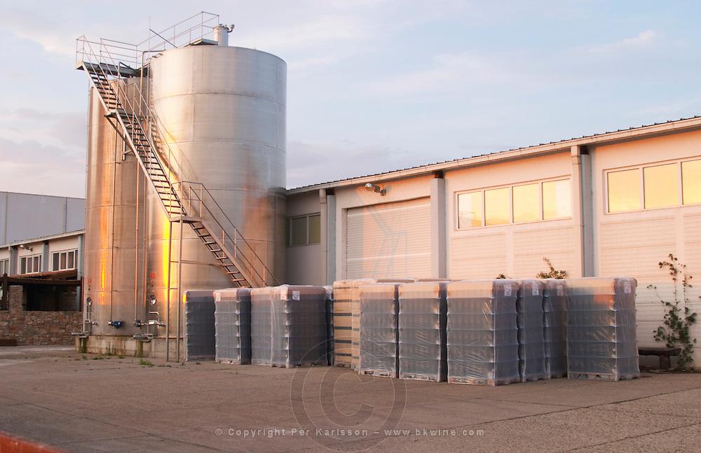 The winery, big stainless steel fermentation tanks outside and pallets with bottles. Hercegovina Produkt winery, Citluk, near Mostar. Federation Bosne i Hercegovine. Bosnia Herzegovina, Europe.