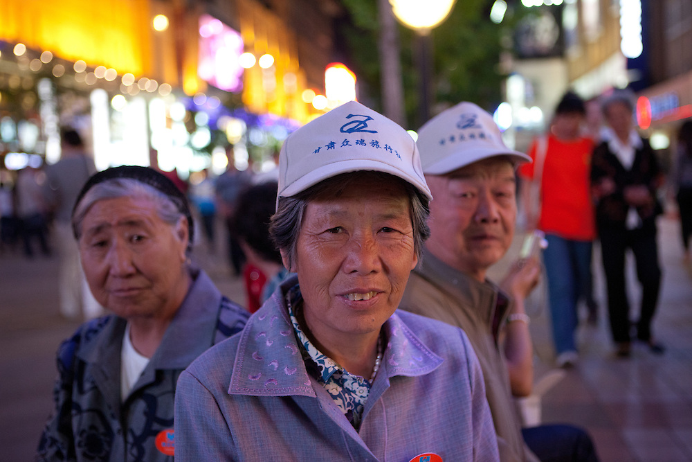 Members of a Chinese travel group are relaxing on a bench located at a public square in the center of Beijing. Beijing is the capital of the People's Republic of China and one of the most populous cities in the world with a population of 19,612,368 as of 2010.