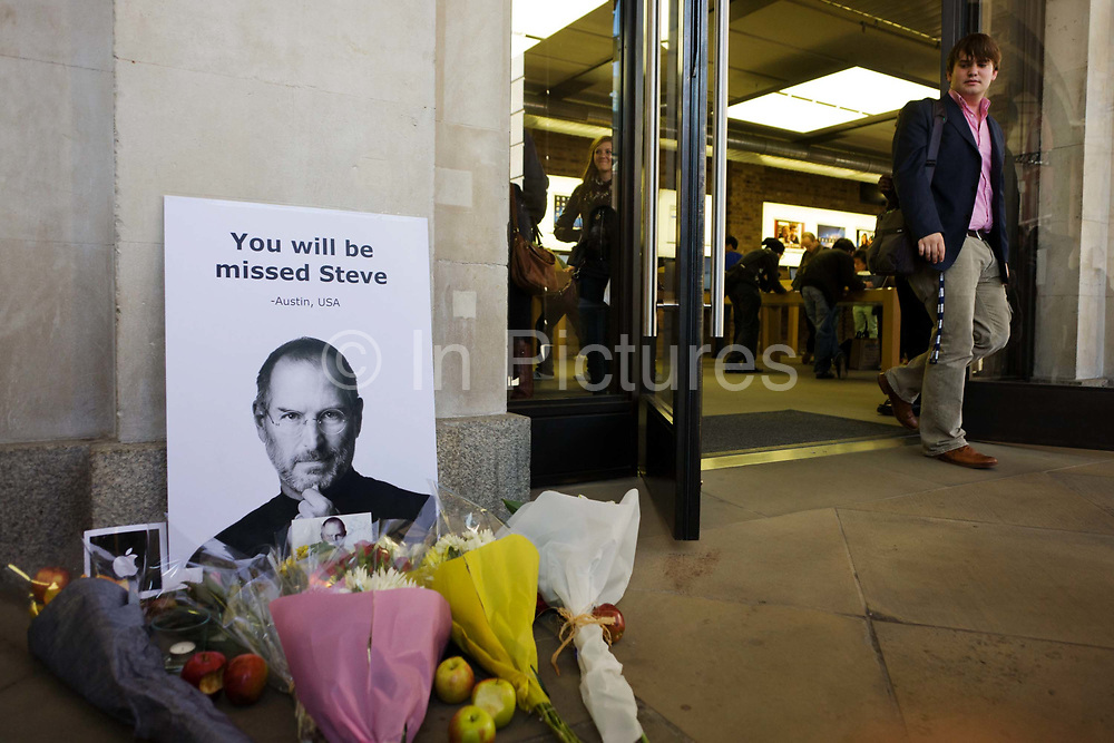Customers walk past the makeshift shrine, where Londoners commemorate Apple's creator Steve Jobs the morning after hearing of his death overnight from pancreatic cancer  at the age of 56 on the 6th Oct 2011. This Apple Store in the capital's Covent Garden, one of the first to be built in Europe and serves as a flagship outlet for the stylish brand of computer accessories that were largely the brainchild of Jobs who started the company as a student in 1977.