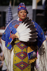 North America, USA, Washington, Seattle. Native American woman at powwow wears beaded cloak and holds fan of eagle feathers