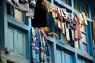 A young boy looks out through the window of his family home in Ropa Village in Himachal Pradesh, India
