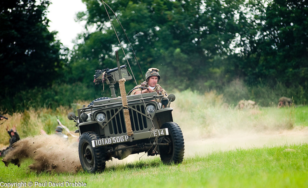 """Re-enactor from the Northern World War Two Association Living History group portraying a member of the American 101st Airborne """"Screaming Eagles"""" speeds across the battlefield in a Willys Jeep mounted with a Browning 30 caliber machine gun during a large scale battle re-enactment. SPAM 1940's Weekend. Heckmonwyke near Wakefield 10 July 2010 .Images © Paul David Drabble."""