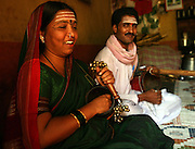 """Radhabai Madar Mudalagi (left) was dedicated as a Devadasi by her parents at a very young age.  Now in her early forties, she lives in the small village of Yellamanawadi and uses the Devadasi musical tradition called """"Chowdike Pada"""" to educate her audiences about social issues, particularly, the Devadasi system. Accompanied by her husband, Mrutunjaya Mudalagi, (right) who plays an instrument called the shruti that resembles a guitar, Radhabai was even recorded for a television program which was broadcasted to small villages all over Karnataka and other states as part of a social education program.  Because of her activism coupled with the fact that she defied the Devadasi system and married a man, she has been rejected by her community.."""