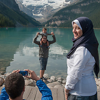 Tourists photograph their family at Lake Louise in Banff National Park, Alberta, Canada.