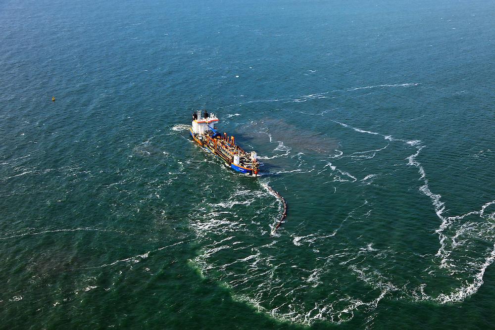 Nederland, Zuid-Holland, Gemeente Westland, 23-05-2011; Delflandse Kust ter hoogte van Ter Heijde en Monster. Sleephopperzuiger verbonden met de persleiding die naar de kust loopt. Het schip voert zand aan voor de aanleg van de Zandmotor: aanleg van kunstmatig schiereiland door het opspuiten van zand voor de kust. Wind, golven en stroming zullen het zand langs de kust verspreiden waardoor breder stranden en duinen ontstaan. De zandmotor is een experiment in het kader van kustonderhoud en kustverdediging. In de achtergrond de kassen van het Westland..A trailing suction hopper dredger before the coast of Holland, connected to the discharge pipe that runs to the shore. Building of the Sand Engine, construction of artificial peninsula by the raising of sand for the coast of Ter Heijde (near the Hague, at the horizon). Wind, waves and currents will distribute the sand along the coast yielding wider beaches and dunes along the coastline. The Sand Engine is a experiment for coastal maintenance of coastal defense. In the background the Westland greenhouses..luchtfoto (toeslag); aerial photo (additional fee required).foto Siebe Swart / photo Siebe Swart