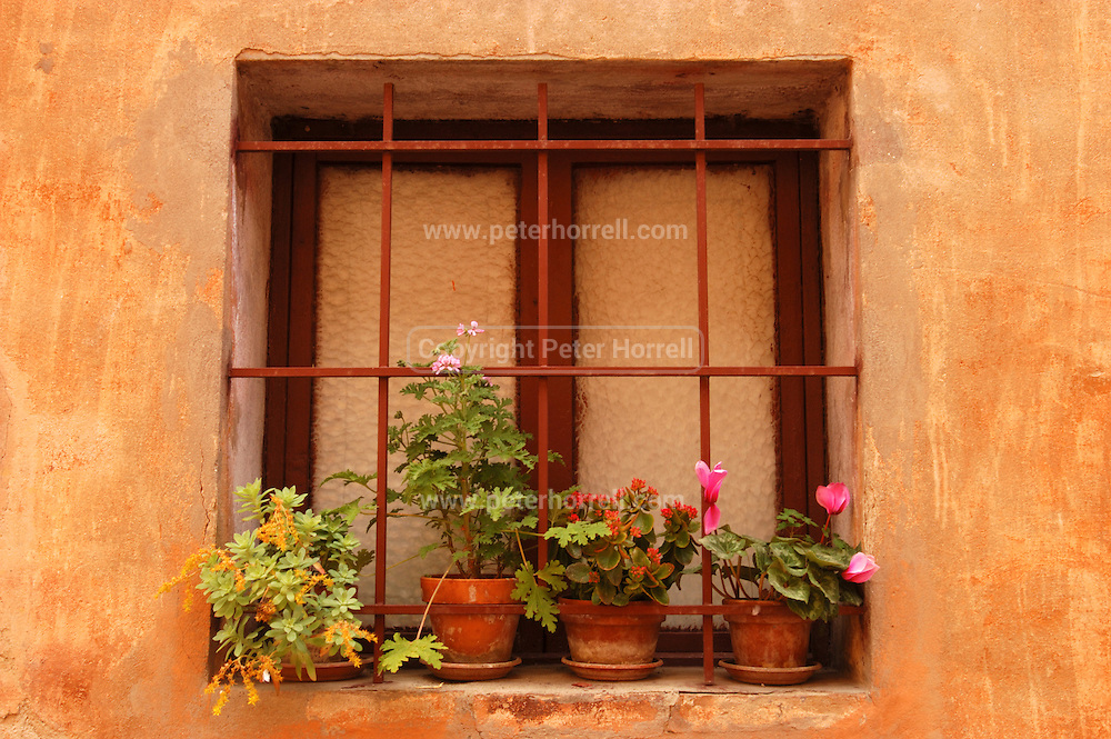 San Gimignano - Monday, May 10 2004: Window frame with potted flowers and bars. (Photo by Peter Horrell / http://www.peterhorrell.com)