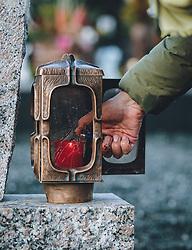 THEMENBILD - eine Frau zündet eine Kerze in einer Laterne an. Am 1. November gedenken Katholiken aller Menschen, die in der Kirche als Heilige verehrt werden. Das Fest Allerseelen am darauf folgenden 2. November, ist dem Gedaechtnis aller Verstorbenen gewidmet, aufgenommen am 30. Oktober 2020 in Kaprun, Oesterreich // a woman lights a candle in a lantern. On All Saints' Day November 1, Catholics remember all people who are venerated as saints in the church. The festival Souls on the following November 2 is dedicated to the memory of all deceased, taken at the cemetery in Kaprun, Austria on 2020/10/30. EXPA Pictures © 2020, PhotoCredit: EXPA/Stefanie Oberhauser