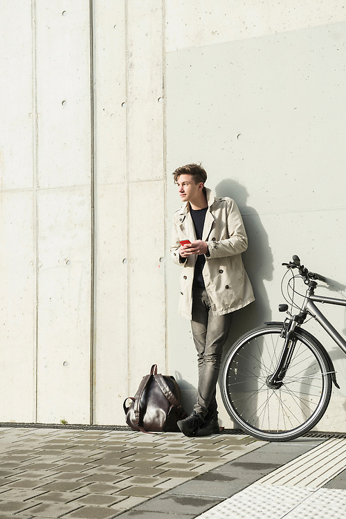 Young man text messaging on smart phone and leaning against concrete wall, Munich, Bavaria, Germany