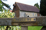 Sign reads Peace Be at St Bartholomew church in Wanborough, Surrey, UK. Originally a Saxon church, it was rebuilt in the 12th century and is a beautiful and simple chapel originally built for the monks of Waverley Abbey. It now serves the rural parish of Wanborough, as part of the United Parish of Seale, Puttenham and Wanborough.