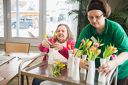 Caretaker and senior woman arranging flowers and vases at rest home