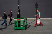 Man with striped jacket with a lamp post shadow against a grey construction hoarding in central London's Trafalgar Square.