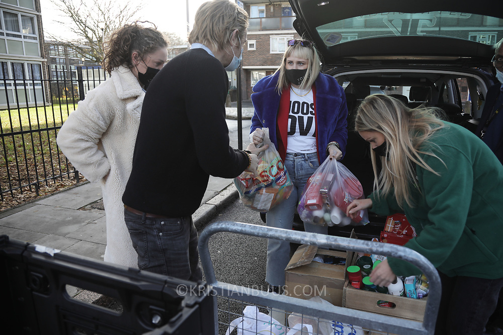 Workers and volunteers at Hackney Foodbank receive and organize food donations, 15th of December 2021, Hackney, East London, United Kingdom. Two women hand over food donations to food bank workers. The Hackney Foodbank is part of a nationwide network of foodbanks, supported by The Trussell Trust, working to combat poverty and hunger across the UK. The food bank gives out three days emergency food supplies to families and individual who go hungry in the borrough. The food is all donated by individuals and the food donated is held in a small ware house where it is  sorted and packed for distribution.  More people than ever in Britain have turned to the food bank for help and in Hackney the need has gone up with 350% over the past two years.