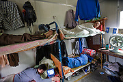 Welder Huang Neng (top left) and his fellow workers rest in the living quarters of a construction company in the fast-growing Pudong area of Shanghai, China. (Huang Neng is featured in the book What I Eat: Around the World in 80 Diets).  Living quarters and food services are on site, and at least 10 workers share one room. In China, migrant laborers often live directly on the job-site grounds of big construction projects and work 12-hour shifts, seven days a week. Alcohol is only tolerated in the company cafeteria after dinner.
