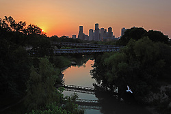 Sunrise from the Rosemont Bridge over Buffalo Bayou with skyline of downtown Houston, Texas.