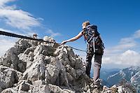 Female hiker on via-ferrata (klettersteig) route of Mittenwalder Hoehenweg in the Karwendel group of Northern Limestone Alps, Mittenwald, Bavaria, Germany