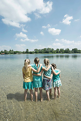 Group of friends standing in lake, Bavaria, Germany
