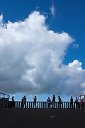 Tourists silhouetted against cloud formations at Pali lookout
