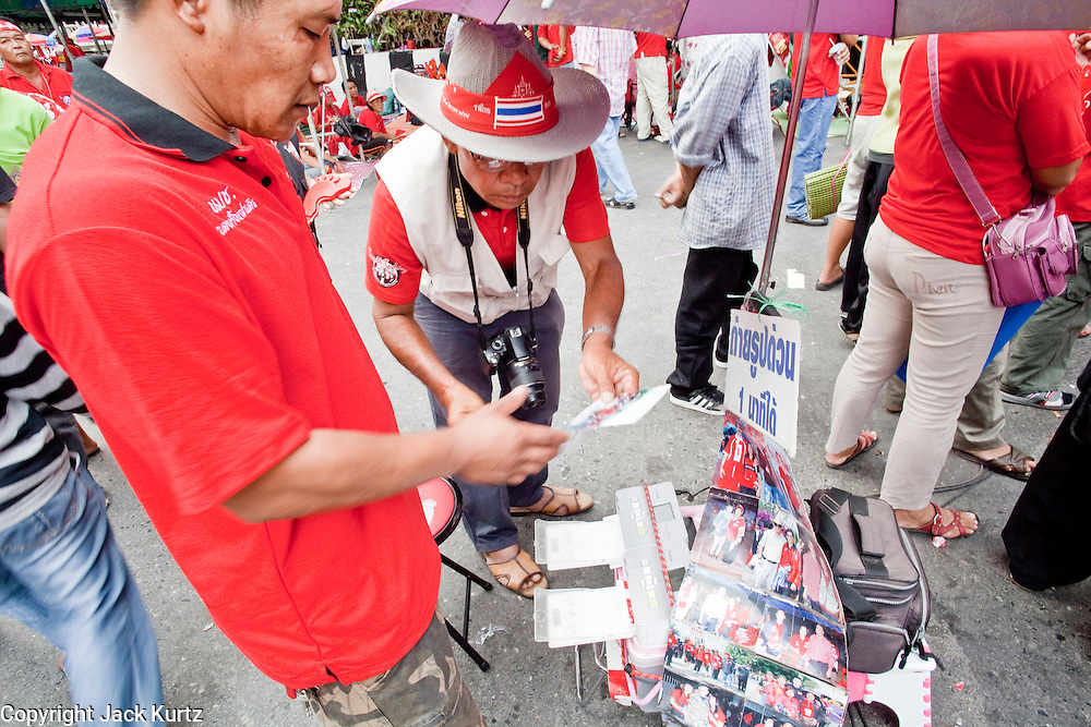18 APRIL 2010 -- BANGKOK, THAILAND: A photographer with a digital camera sells prints off of a Canon Selphy printer to Red Shirt protestors. The Red Shirts protest in the Ratchaprasong Shopping district, home to Bangkok's most upscale malls, is costing the Thai economy millions of Baht per day because the malls and most of the restaurants are closed and tourists are staying away from the area. But that hasn't stopped the Red Shirts who have brought their own economy with them. There are Red Shirt restaurants, food stands, souvenir vendors and more, creating a micro economy for Red Shirts in the area.  The Red Shirts continue to occupy Ratchaprasong Intersection an the high end shopping district of Bangkok. They are calling for Thai Prime Minister Abhisit Vejjajiva to step down and dissolve the parliament. Most of the Red Shirts support ousted former Prime Minister Thaksin Shinawatra.   PHOTO BY JACK KURTZ