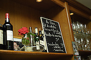Shelf in a bar with bottles glasses flower and chalk board. Wine bar les Enfants Rouges in Paris. Paris, France.