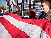 """07 DECEMBER 2010 - PHOENIX, AZ:  Supporters of the DREAM Act hold up a large American flag in front of the offices of US Sen. John McCain in Phoenix Tuesday. Dolores Huerta, who started working in the civil rights movement in the 1960's, threw her support behind students fasting on behalf of the DREAM Act in front of Sen. John McCain's office Tuesday. The student picked McCain's office because he used to support the DREAM Act. They hope that the US Senate will pass the DREAM Act during its """"lame duck"""" session. The Senate debated and defeated similar legislation just before the November general election.   PHOTO BY JACK KURTZ"""