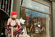 "A mannequin in a red wig and red fetish wear in front of ""He and She"", a shop on Toronto's Queen Street East."