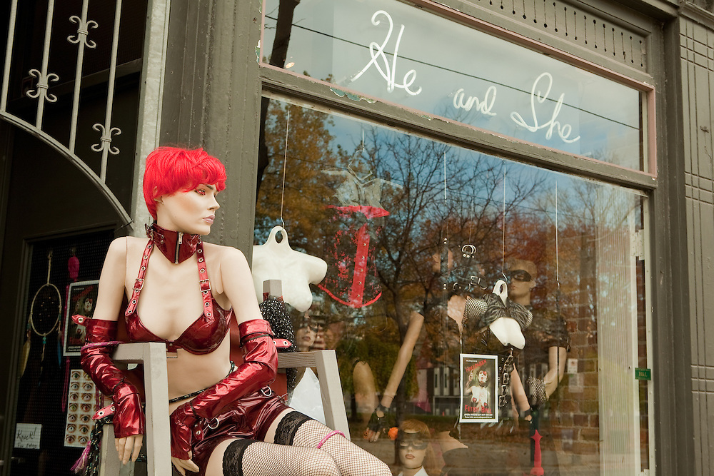 """A mannequin in a red wig and red fetish wear in front of """"He and She"""", a shop on Toronto's Queen Street East."""