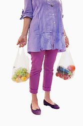 Senior woman holding fruits and vegetables in plastic bag