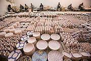 """Painters, each with his own traditional design assignment applies color to bisqueware at Morvarid (Pearl) Pottery Factory, Meybod,  Iran. (Also spelled """"Maybod"""")."""