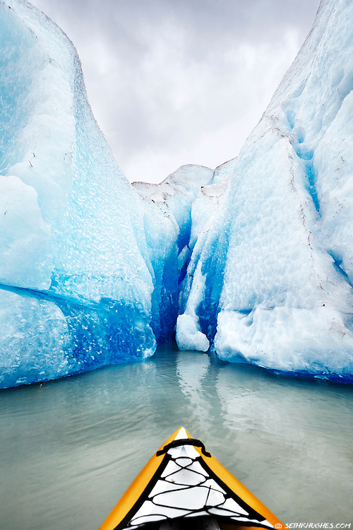 A kayaker admires an extreme, up-close view of the ice on Mendenhall Glacier near Juneau, Alaska.