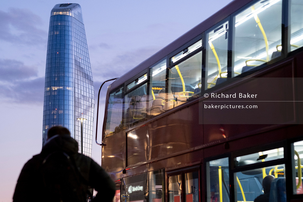 Seen from the City of London, One Blackfriars (one of the capital's newest skyscrapers) rises above a pedestrian and London bus during the evening rush-hour, on 26th February 2021, in London, England. Located on Bankside, the south bank of the river Thames, the development is a 52-storey 170m tower whose uses include residential flats, a hotel and retail.
