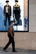 A man wearing a mask walks by a retail store on Collins Street during COVID-19. After seeing another 177 cases overnight and further outbreaks in nursing homes, Metropolitan Melbourne and the Mitchell Shire are in lockdown following the rise of active cases to 1,612. The new restrictions came into effect on Thursday 9 July with residents in lockdown areas under stay at home orders for the next six weeks. (Photo be Dave Hewison/ Speed Media)
