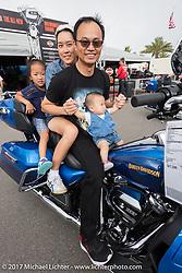 Harley-Davidson employee Steve Slater takes a photo of Ray Chaijirawat and his family at the Harley-Davidson dispay at the Daytona Speedway during Daytona Beach Bike Week. FL. USA. Sunday March 12, 2017. Photography ©2017 Michael Lichter.
