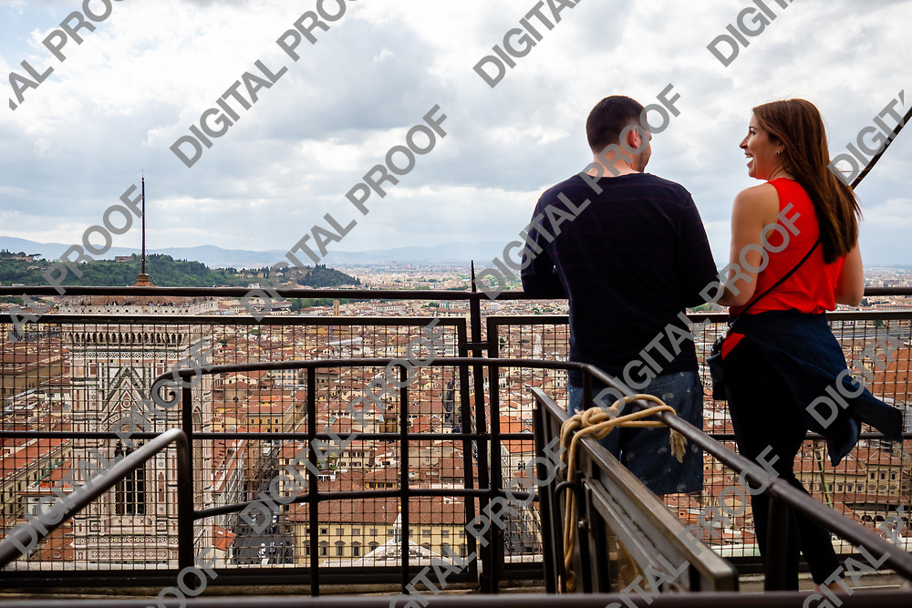 A couple enjoys the view of Florence - Firenze - from the lookout observation point of the Duomo in Florence, Tuscany Region - Italy
