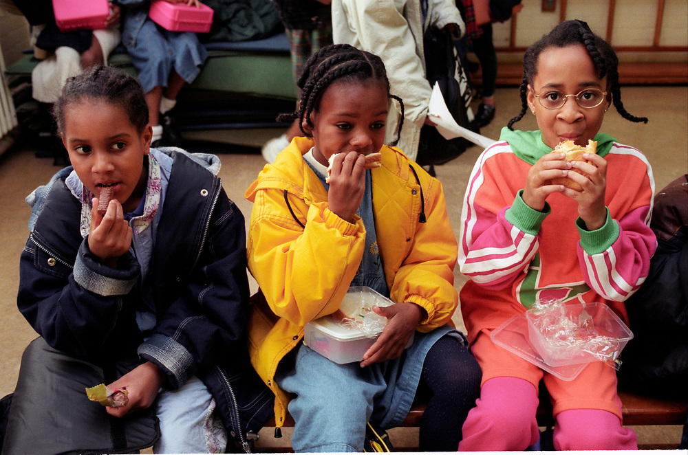 three girls sitting eating their packed lunches,
