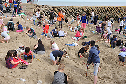 "© Licensed to London News Pictures. 30/08/2014<br /> Folkestone Gold Beach.<br /> £10,000 of buried treasure at Outer Harbour beach near Sunny Sands, Folkestone,Kent.<br /> The installation, entitled ""Folkestone Digs"", is funded by Bristol-based designers Situations and the idea for the project came from Berlin-based artist Michael Sailstorfer.<br /> The small gold bars - similar to a dog tag - come in two sizes, worth around £250 and £500.<br /> <br /> (Byline:Grant Falvey/LNP)"