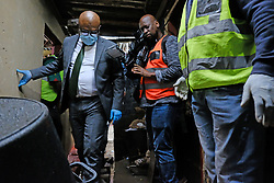 JOHANNESBURG, SOUTH AFRICA - APRIL 14: Johannesburg Mayor, Geoffrey Makhubo enters a flooded passageway. The mayor visited Alexandra to address community concerns from the effects of the national lockdown on April 14, 2020 in Johannesburg South Africa. Under pressure from a global pandemic. President Ramaphosa declared a 21 day national lockdown extended by another two weeks, mobilising goverment structures accross the nation to combat the rapidly spreading COVID-19 virus - the lockdown requires businesses to close and the public to stay at home during this period, unless part of approved essential services. (Photo by Dino Lloyd)