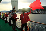 Crew members welcoming other Hurtigruten ferry ship at Molde, Norway