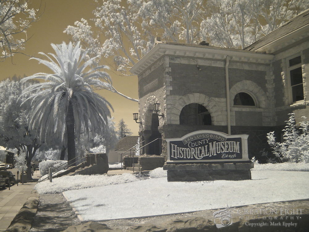 Funds for the construction of the Carnegie Library building were provided by a grant of $10,000 from steel tycoon Andrew Carnegie, who funded the establishment of some 3,000 libraries worldwide. The Museum building was designed by W.H. Weeks, an architect from Watsonville , California , and was built by the construction firm of Stephens and Maino of San Luis Obispo. The structure's sandstone was brought from Los Berros, near Arroyo Grande. The granite in the building was quarried from nearby Bishop's Peak and brought into the city on a spur of the narrow gauge Pacific Coast Railway. The Museum is the only building in San Luis Obispo County built with both of these local stones...When a search for a permanent home for the Museum was undertaken in 1953, the newly formed San Luis Obispo County Historical Society received assistance from the San Luis Obispo City Council and the County Board of Supervisors. An agreement was struck regarding the old library building, and in 1956, the San Luis Obispo County Historical Museum was opened to the public. .Information from: https://slochsorg.secure.myhosting.net..This is an infrared image which captures light that we cannot see and turns it into a visible image. Plants like flowers and grass reflect more infrared light and appear brighter in infrared images while the sky reflects less making it darker.