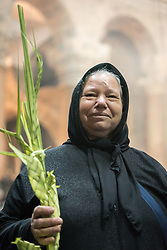 20 April 2019, Jerusalem: A woman holds up a palm leaf, as one of many Orthodox Christians marking Palm Sunday in the Church of the Holy Sepulchre.