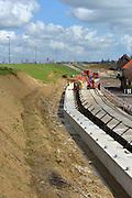 Nederland, Streefkerk, 30-3-2016Achter de Lekdijk, die onvoldoende bestand bleek tegen heel veel water, wordt her en der een verzwaring aangebracht om de stabiliteit te garanderen. Op verschillende plekken worden verschillende technieken toegepast. Veelal wordt de ijk aan de basis verstevigd en gestabiliseerd door diepe betonnen en stalen ankers in de grond, afgedekt met een grote betonnen rand.  Om het kwelwater af te voeren zijn op verschillende stukken honderden buizen ingebracht die een horizontale drainage moeten opleveren . Ook wordt in dit dijkvak een klimaatdijk aangelegd .Foto: Flip Franssen/ HH