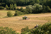 distant view of a combine harvesting wheat crop